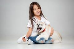 Portrait d'une petite fille joyeuse ayant l'amusement avec le chiot enroué sibérien sur le plancher au studio photos libres de droits