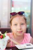 Portrait d'une petite fille mangeant des sushi dans le restaurant asiatique Image libre de droits