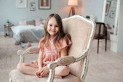 Portrait d'une petite fille mignonne s'asseyant dans la chaise dans sa chambre Photographie stock libre de droits