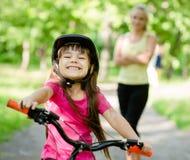 Portrait d'une petite fille montant son vélo en avant de sa mère Photo stock