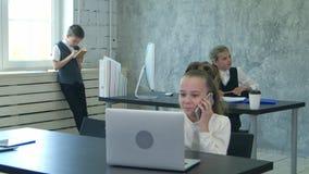 Portrait d'une petite fille parlant au téléphone et travaillant sur l'ordinateur portable dans le bureau clips vidéos