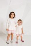 Portrait d'une petite fille qui tient sa main du ` s de soeur sur un fond blanc dans le studio Photo libre de droits