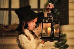 Portrait d'une petite fille regardant la bougie dans la lanterne Images stock