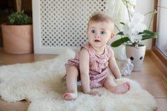 Portrait d'une petite fille s'asseyant sur le plancher photographie stock libre de droits