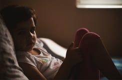 Portrait d'une petite fille sur le lit images stock