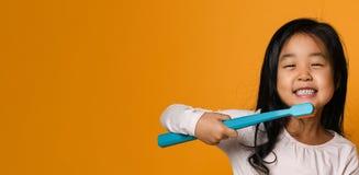 Portrait d'une petite fille tenant une brosse à dents au-dessus de fond jaune photos libres de droits