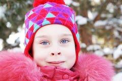 Portrait d'une petite jolie fille portant les vêtements roses extérieurs en hiver Photos stock