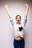 Portrait d'une position, de la main haute et du cri perçant de jeune femme Photographie stock libre de droits