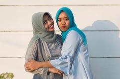 Portrait d'une position gaie de femme de hijab devant un mur blanc Voyez la caméra avec des voisins photographie stock