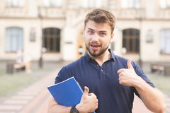 Portrait d'une position positive d'étudiant avec des livres dans des ses mains dans la perspective du bâtiment et du sourire photos stock