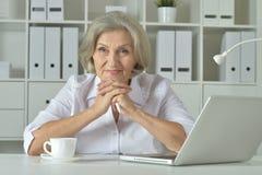 Portrait d'une vieille femme d'affaires à l'aide de l'ordinateur portable Image stock