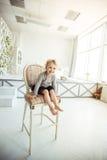 Portrait d'une vieille fille de cinq ans heureuse s'asseyant sur une chaise dans le salon spacieux Photo libre de droits