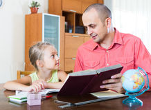 Portrait of dad helping schoolgirl to study Royalty Free Stock Image