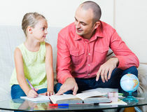 Portrait of dad helping schoolgirl to study Royalty Free Stock Photography