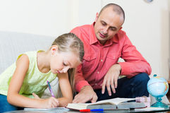 Portrait of dad helping schoolgirl to study Stock Photography