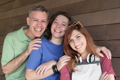 Portrait of Dad with teen daughter and son smiling. Father Day. Portrait of Dad with teen daughter and son embracing each other and smiling. Father Day. Concept stock photo