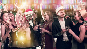 Portrait of dancing females and males in caps and garlands. In the night club Stock Image