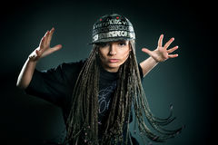 Portrait of dancing girl with dreadlocks in cap. Music and dance concept Royalty Free Stock Image