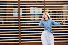 Portrait of a dancing girl with short blond hair and bright pink lips listening to music on a smartphone with striped.  royalty free stock photo