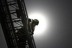 Portrait of danger. Fireman on aerial ladder truck stock photography