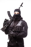 Portrait of dangerous bandit in black wearing balaclava and holding gun in hand. On white Stock Image