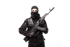 Portrait of dangerous bandit in black wearing balaclava and holding gun in hand. On white Royalty Free Stock Photo