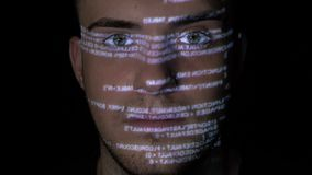 Portrait of a dangerous hacker cyber criminal looking at the camera while running programming code is projected on his face -. Portrait of a dangerous hacker stock video