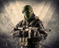 Portrait of a dangerous masked armed soldier with grungy background. Portrait of a dangerous masked armed soldier with grungy light background royalty free stock image