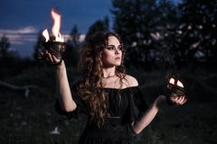 Portrait of dangerous woman. Witch with fire ball and dark make up Royalty Free Stock Image