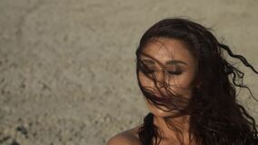 Portrait of a dark-haired tanned woman with hair fluttering in the wind slow motion