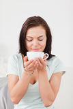 Portrait of a dark-haired woman drinking coffee Stock Images
