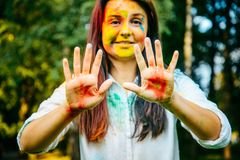 Portrait of dark long hair woman all in holi paints shows her palms Royalty Free Stock Images