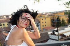 Portrait of a dark short-haired lady, unkempt from the wind, on a balcony with a city background. stock photos
