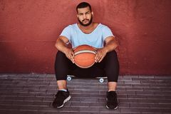 Portrait of a dark-skinned bearded guy dressed in a white shirt and sports shorts sitting on a skateboard with. Basketball and leaning on a wall Stock Images