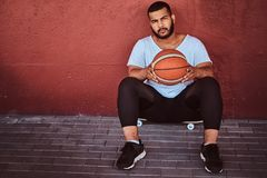 Portrait of a dark-skinned bearded guy dressed in a white shirt and sports shorts sitting on a skateboard with. Basketball and leaning on a wall Royalty Free Stock Photography