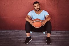 Portrait of a dark-skinned bearded guy dressed in a white shirt and sports shorts sitting on a skateboard with. Smiling dark-skinned bearded guy dressed in a Royalty Free Stock Images