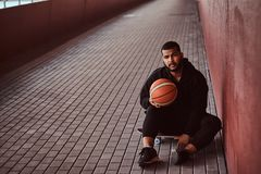 Portrait of a dark-skinned guy dressed in a black hoodie and sports shorts holds a basketball while sitting on a. Skateboard and leaning on a wall Royalty Free Stock Photography