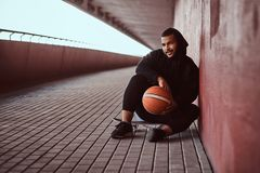 Portrait of a dark-skinned guy dressed in a black hoodie and sports shorts holds a basketball while sitting on a. Smiling dark-skinned guy dressed in a black Royalty Free Stock Photos
