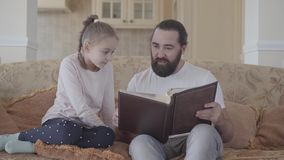 Portrait of daughter and her father sitting in living room and looking photo album with good memories and funny stories. Portrait of small cute daughter and her stock video footage