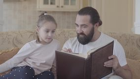 Portrait of daughter and her father sitting in living room and looking photo album with good memories and funny stories. Portrait of small cute daughter and her stock video