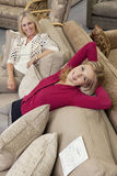 Portrait of daughter relaxing on sofa while mother looking in furniture store Stock Photos