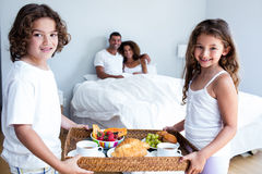 Portrait of daughter and son carrying breakfast tray for parents. In bedroom Royalty Free Stock Image