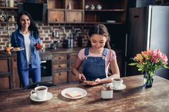 Daughter spreading toast with chocolate paste. Portrait of daughter spreading toast with chocolate paste, helping mother in preparing breakfast in the kitchen Stock Images