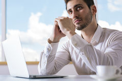 Portrait of daydreaming businessman. Portrait of handsome businessman daydreaming at office desk with laptop and coffee cup Stock Photo