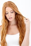 Portrait of daydreaming redhead beauty. Thinking and playing with long curly hair Royalty Free Stock Photography