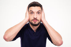 Portrait of dazed bearded young man closed ears by hands Stock Photography
