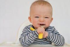 Portrait de bébé apprenant à manger avec la fourchette et la cuillère images libres de droits