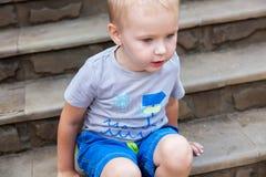 Portrait de beau bébé garçon dehors L'enfant adorable regarde avec l'intérêt quelque chose qui se repose sur l'escalier photos libres de droits