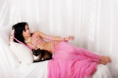 Portrait d'une danseuse du ventre avec un chat siamois Images stock