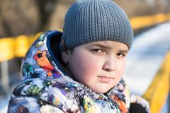 Portrait de beau gros garçon dans le chapeau et la veste d'hiver en parc en hiver Photos stock